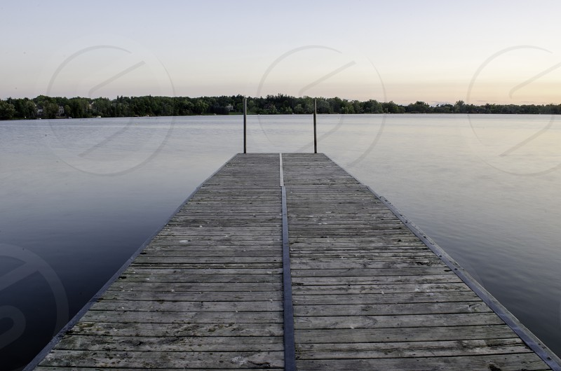 Long exposure picture of the lake out on the dock at sunset.  photo