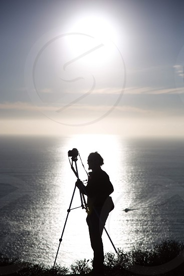 silhouette of man holding tripod with camera near body of water during daytime photo
