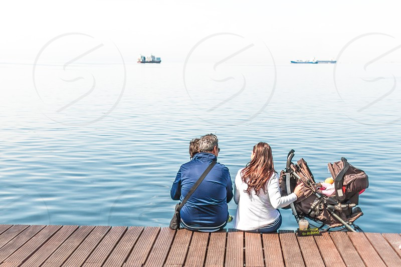 Family Enjoying The View Sitting On The Dock photo