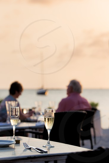 Glasses of champagne on a table at a beach side resort at sunset photo