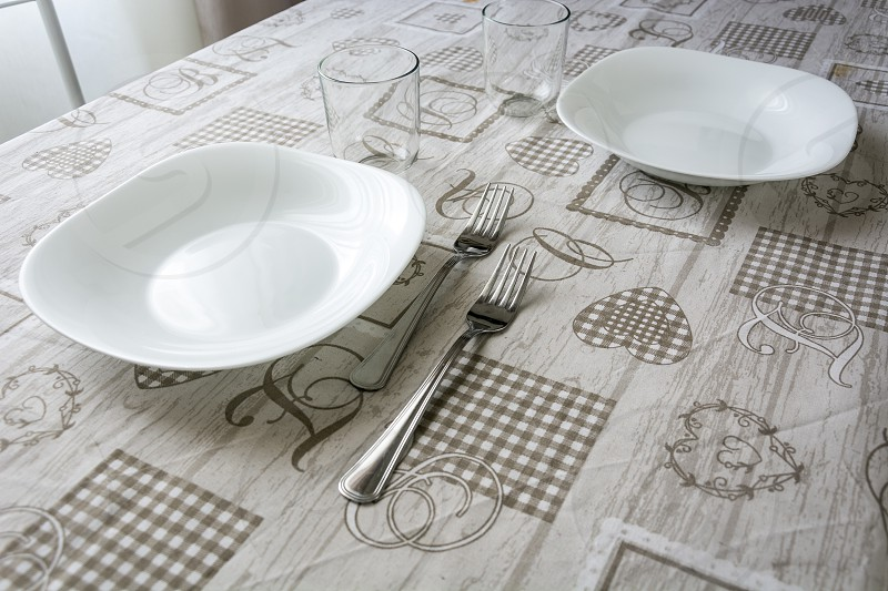 Table set with plates glasses cutlery and tablecloth. Interior shot photo