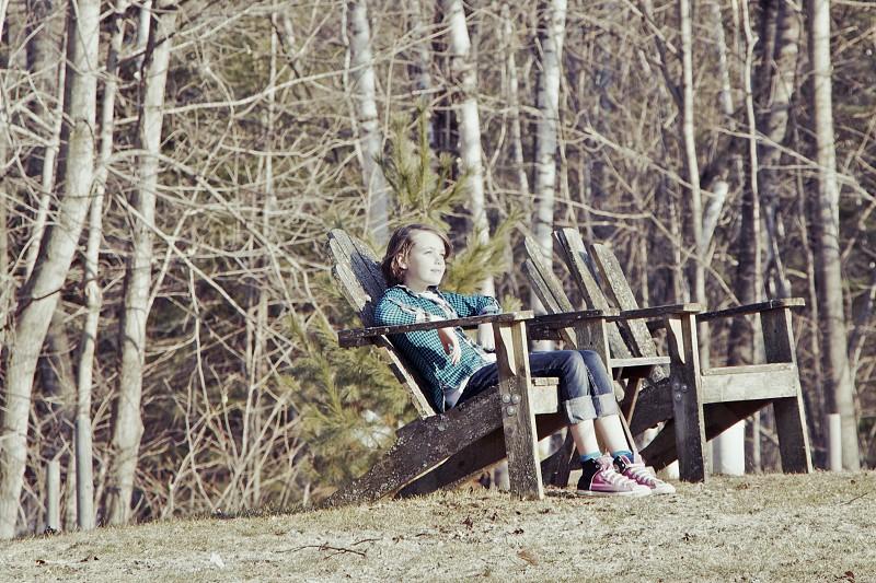 girl wearing green jacket sitting on wooden armchair photo