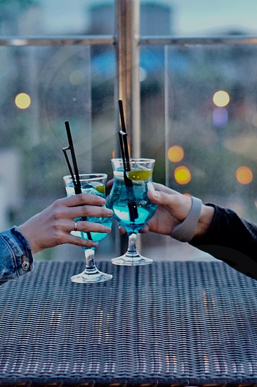 Alcoholic drinks cocktails mixed alcoholic drinks mixed drinks mixed cocktails night date romantic date toast blue lagoon couple  photo