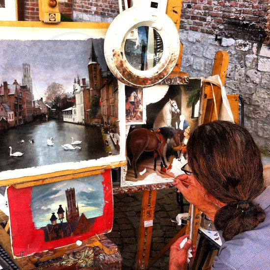 man painting in the streets of Bruges Belgium photo