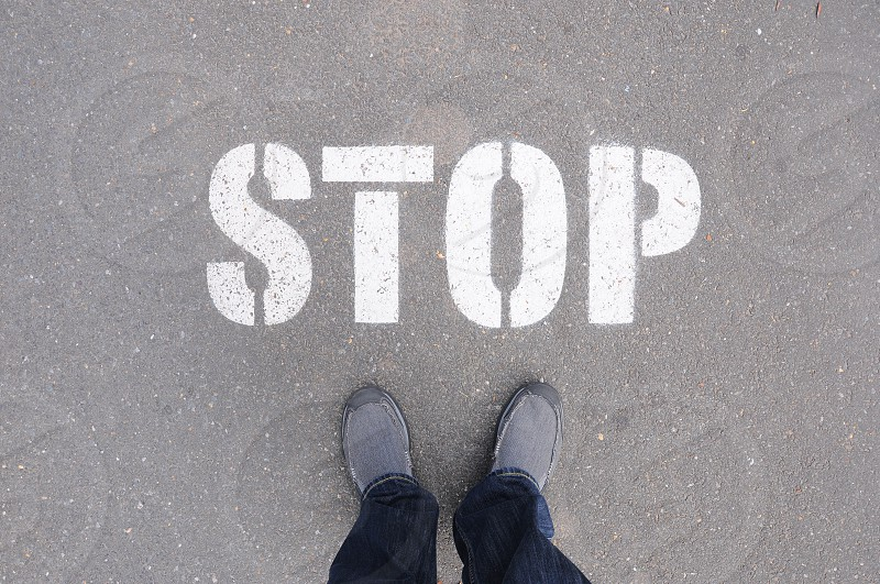 person in black pants wearing black casual shoes in front of stop signage during daytime photo