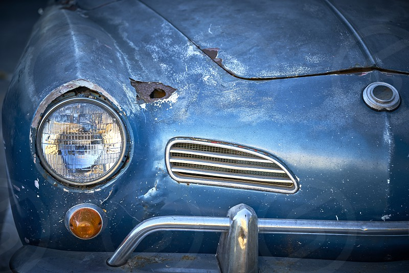 Vintage weathered unrestored blue German classic car with rust hole and tons of character photo