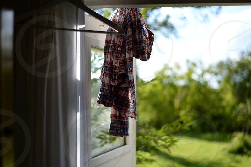 plaid shirt sun light through fabric muted soft colors door open to yard garden photo
