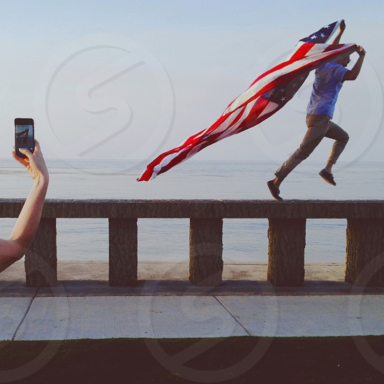 man carrying us flag and running photograph photo