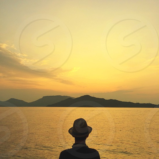 man wearing fedora standing by the water watching the sun set over the mountains photo