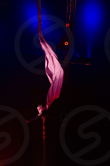 woman doing stunt on a pink textile hanging on roof photo