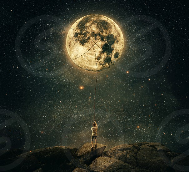 Imaginary view as a young man holding a rope try to catch and pull the full moon from the night sky. Achievement and hard determination concept. photo