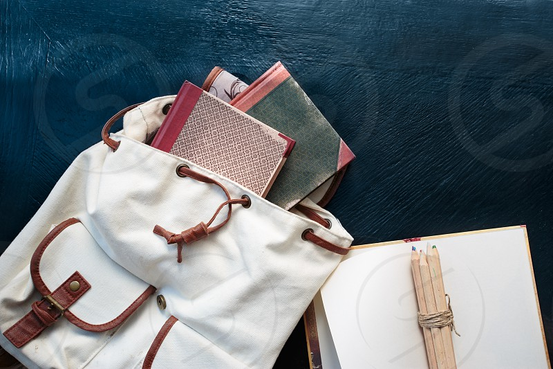 Notebooks pencils and school bag on a desktop photo