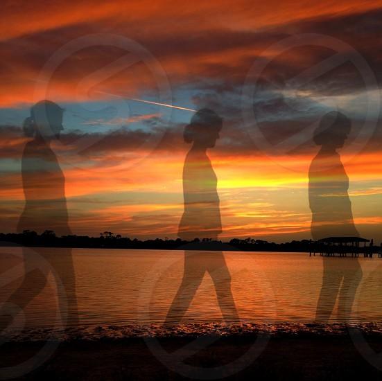 women's shadow walking on seashore photo
