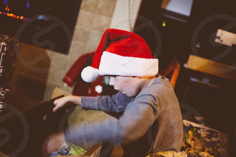boy wearing santa hat and gray long sleeved shirt photo