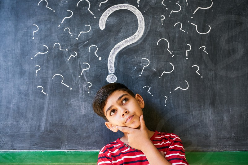 Concepts on blackboard at school. Hispanic boy with doubts and thoughts in class. Portrait of male child thinking against question marks on blackboard photo