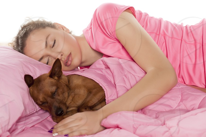 beautiful girl sleeping with her little dog in her bed photo
