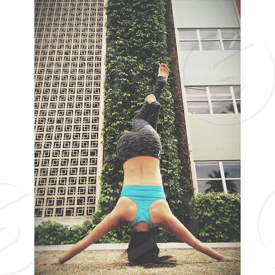 woman in teal sports brassiere doing head stand photo