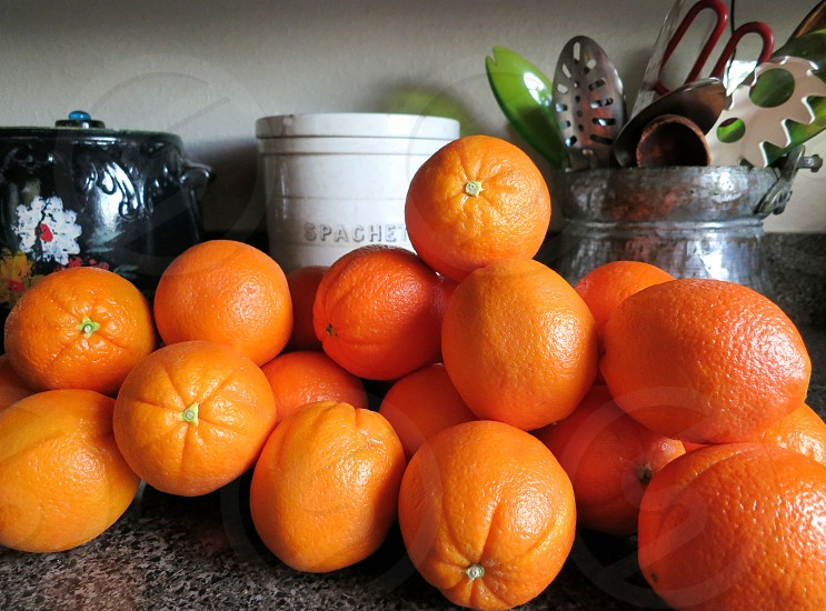 A pile of oranges on kitchen counter  photo