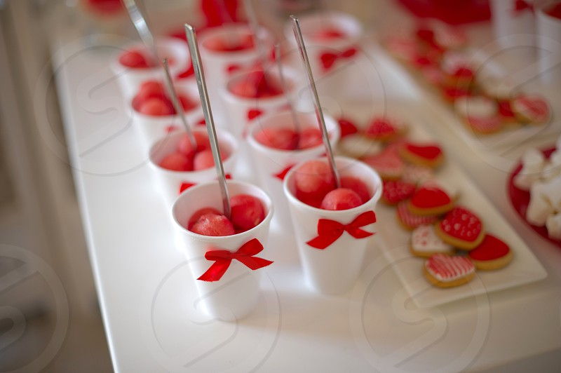 pink desserts in white cups with red bowties photo