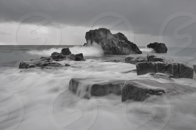 islet covered with fog on grayscale photo