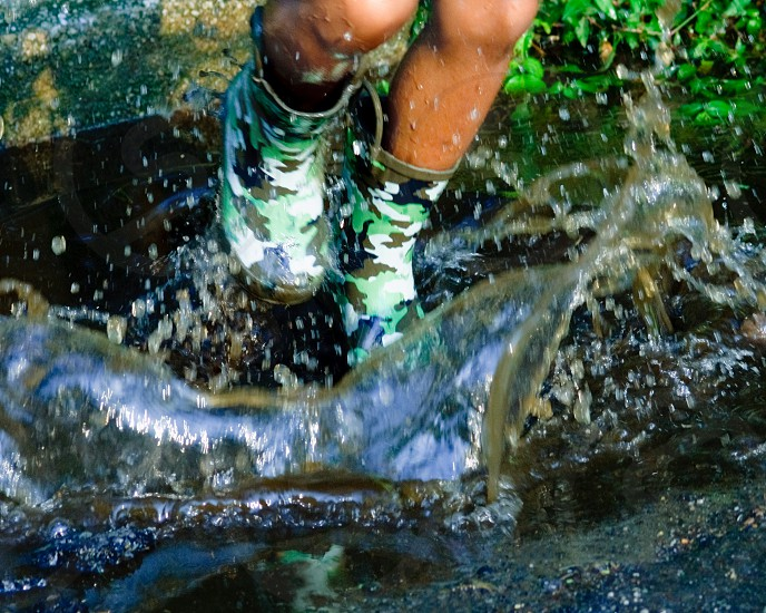 person wearing green white brown and black camouflage rain boots walking along stream photo