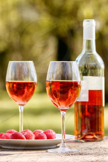Two glasses partially filled with rosé wine a bottle of rosé wine a plate with strawberries laid on a table outdoor. Trees can be seen out of focus in the background. photo