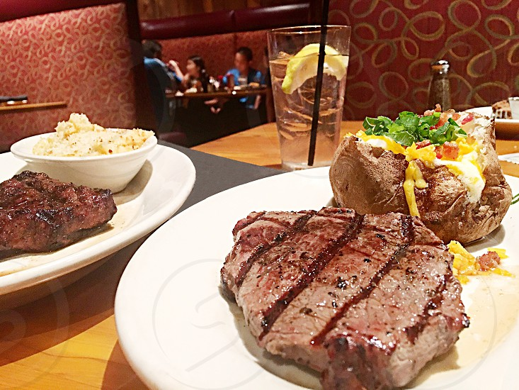 Perfectly grilled steak and loaded baked potato. photo