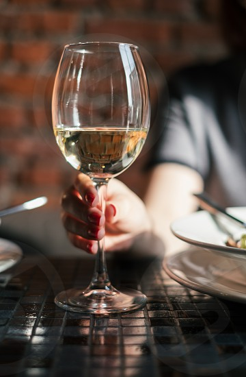 Woman holding glass of white wine photo