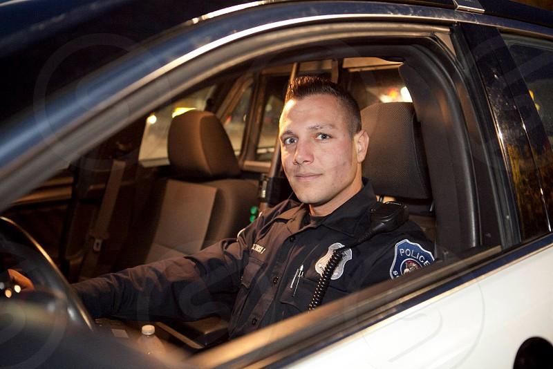 man wearing black police uniform riding on white car at night photo