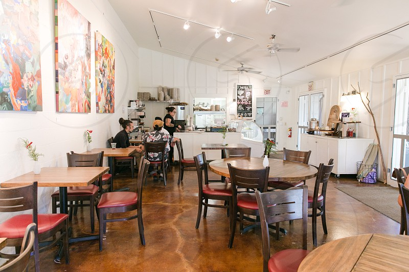 2 person eating on white painted wall restaurant with floral wall painting and brown wooden tables photo