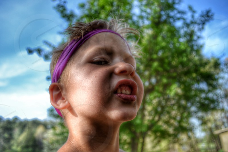 young boy in purple headband making mean silly face with head back photo