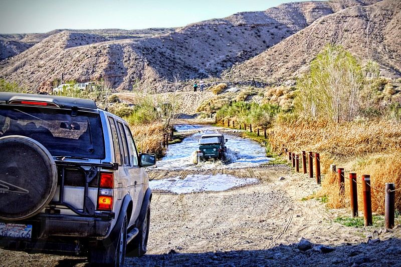 Seen from a car behind a jeep caravan drives over water in a desert environment photo