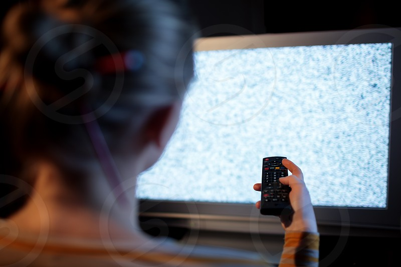 Back view of woman with remote control in front of TV set with noise on the screen photo