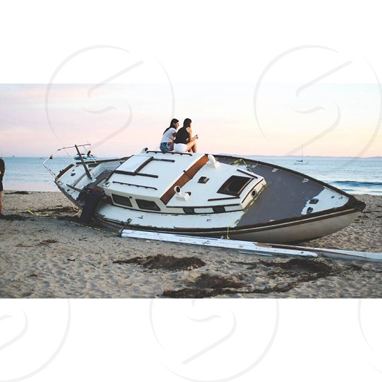 2 women sitting on white speedboat photo