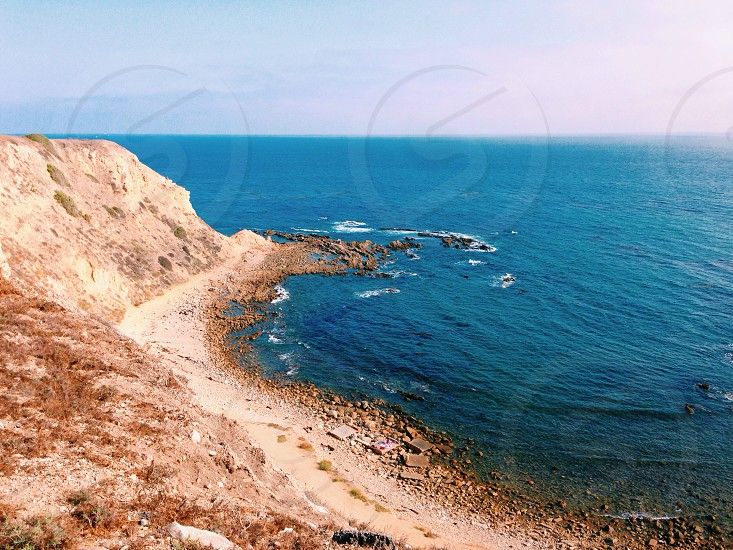 brown mountain and blue ocean photo