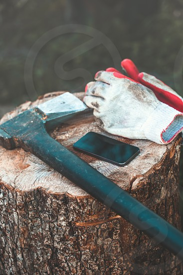 Mobile phone and tools axe work gloves on tree trunk photo