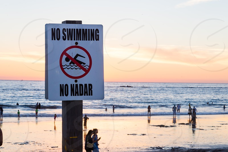 Ironic no swimming sign in front of beachgoers swimming in the waves photo