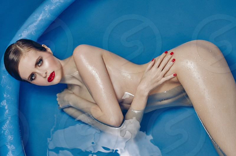 naked woman with red manicure lying on above ground swimming pool photo