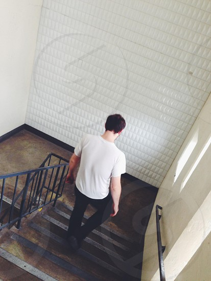 Man walking down stairs stairs neutral grey journey man movement photo