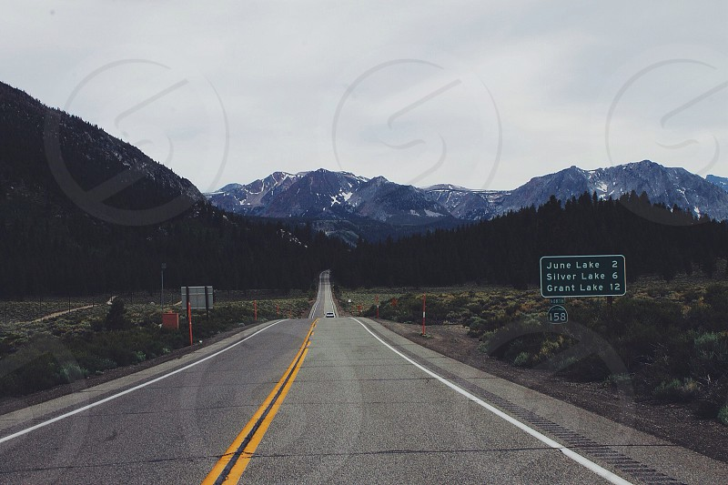 single lane highway double yellow line in road cloudy sky driving towards mountains photo