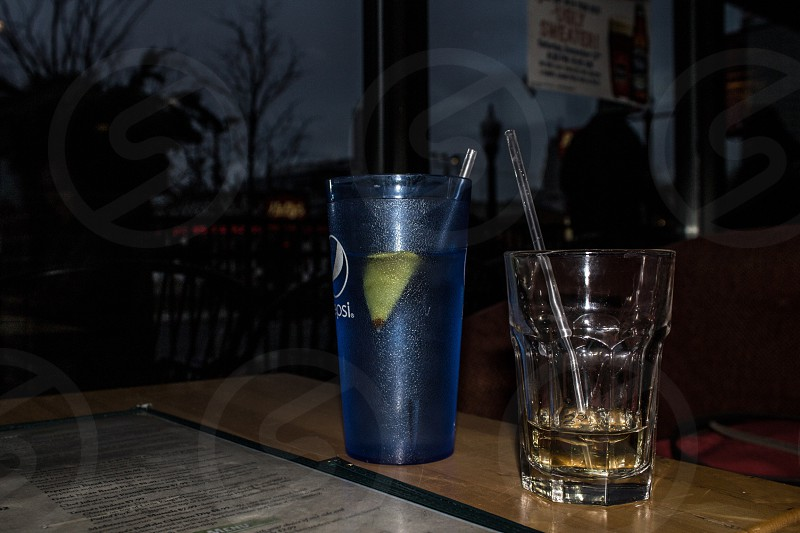 blue Pepsi drinking glass on table near clear drinking glass photo