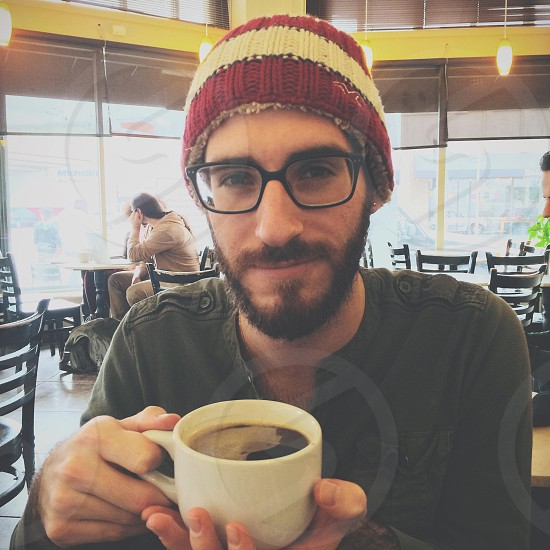 man wearing white and brown beanie and black framed eyeglasses inside coffee shop photo
