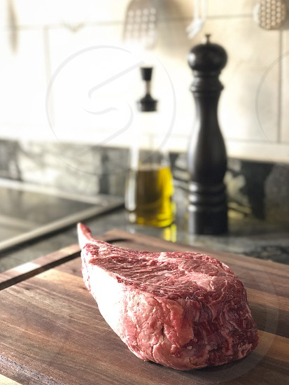 Close up of raw thick tomahawk ribeye beef steak on cutting board. Oil dispenser and pepper mill in the background. photo