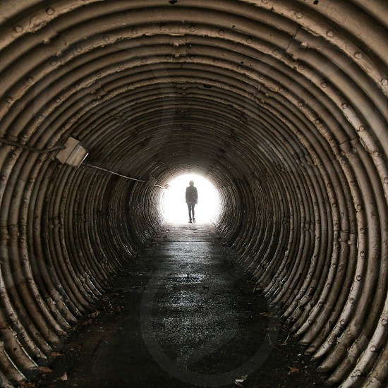 Person standing at the end of a tunnel. photo