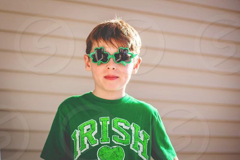 boy in green shamrock glasses on st patrick's day photo