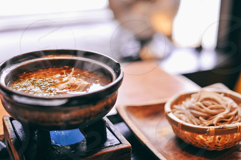 steaming bowl of soup on a raised platform on a tray with noodles in a bowl photo