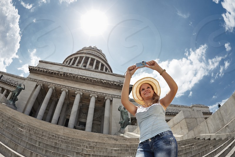 young woman as tourist in La Habana Cuba taking pictures of monuments near the Capitolio photo