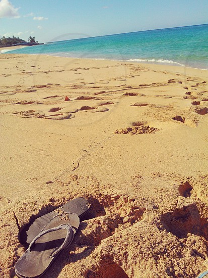 Sandy footprints on golden colored sand with turquoise waves inviting you to new adventures. photo