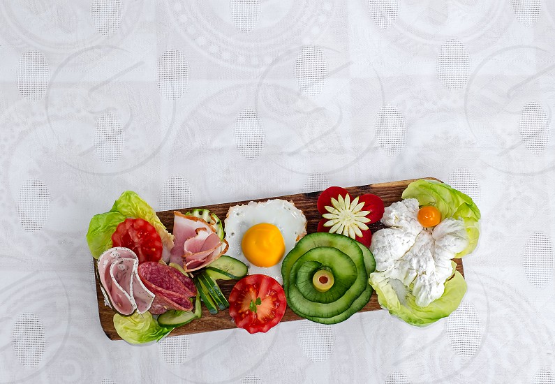 Breakfast on wooden platter - Fresh cheese on lettuce with fried egg cucumber tomato ham and green olives. White silk tablecloth background.  photo