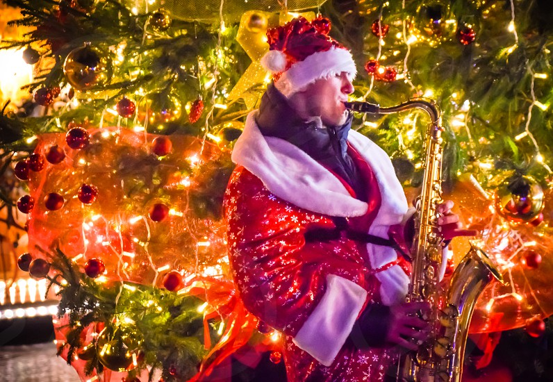 Cheerful Santa Claus Playing Saxophone Music In Front Of A Christmas Tree To Celebrate New Years Eve  photo